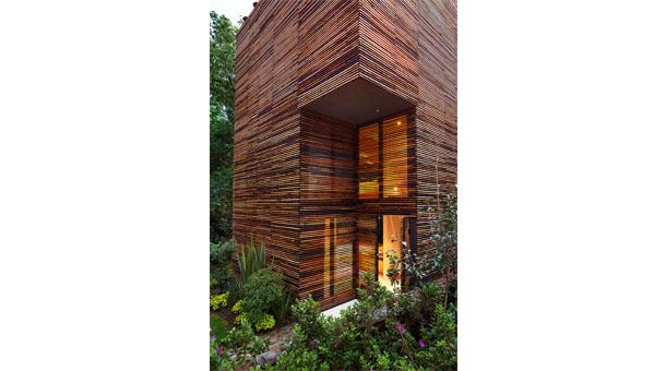 Casa Chipicas. Una piel de madera cubre las áreas de servicios, mientras que las zonas que dan hacia el jardín interior están cubiertas con vidrio.