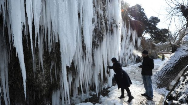 En Georgia las temperaturas comenzaron a ceder desde inicios de febrero. Esta imagen capturada la semana muestra una zona rocosa recubierta de hielo. La pareja de la fotografía experimenta una temperatura de -7º C. (Foto: AFP)