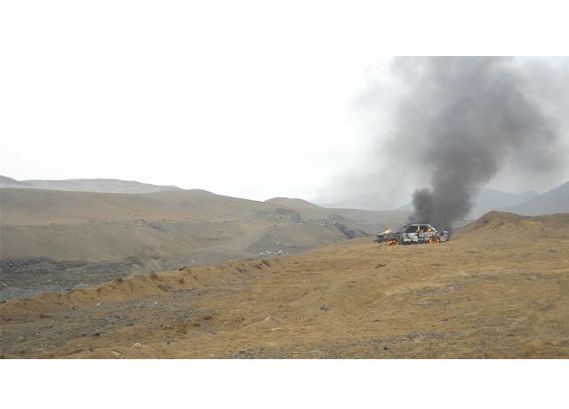 Desolación. Un auto arde en medio de un basural en el desierto. (Foto: Galería 80m2)