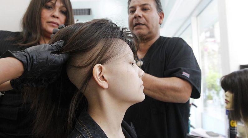 """El estilista Marcelo Avatte (derecha) prepara una peluca que usará Isidora Serrano, una chica de 14 años que perdió su cabellera durante el tratamiento de quimioterapia para tratar su cáncer a los huesos en el hospital Luis Calvo Mackenna en Santiago. Avatte, conocido en su país como """"el rey de las pelucas"""" inició un proyecto en el 2009 y ha donado 300 pelucas para niños y adolescentes con cáncer. (Foto: REUTERS/Rodrigo Garrido)"""