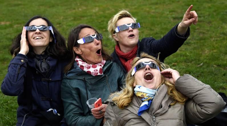 Ciudadanas europeas bromeando sobre el eclipse al no poder observarlo debido a las nubes. (Foto: AFP PHOTO / DOMINIQUE FAGET)