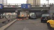 Camión atascado en puente de Av. Brasil con cartel 'solo autos'