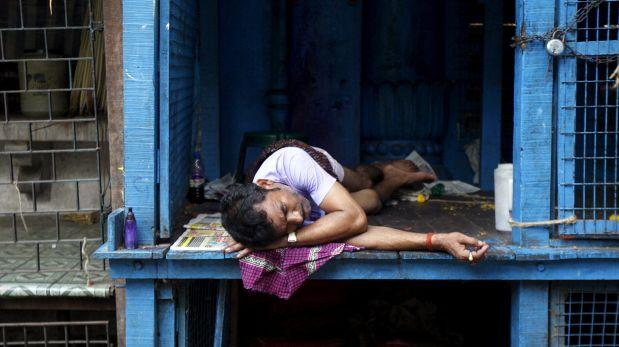 La gente busca cualquier refugio para protegerse del intenso calor. Este vendedor de flores descansa en su puesto de venta. (Reuters)