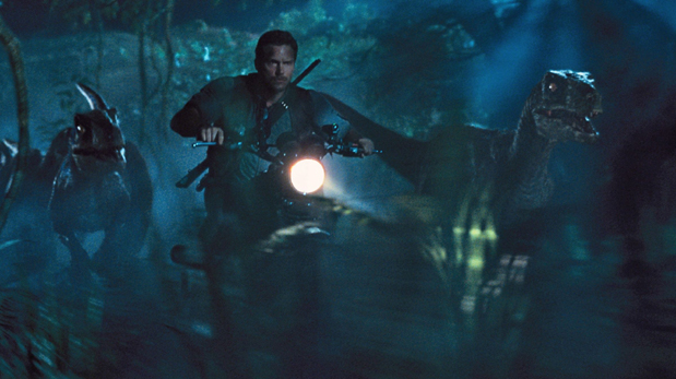 This photo provided by Universal Pictures shows, Chris Pratt as Owen leading the raptors on a mission in a scene from the film,