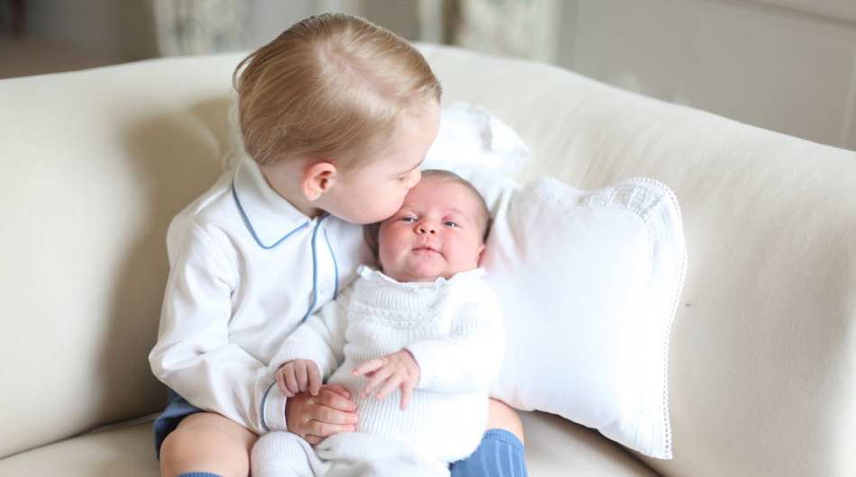 This image made available by Kensington Palace Saturday, June 6, 2015, taken by Kate, Duchess of Cambridge, at Amner Hall, eastern England in mid-May 2015 shows Britain's Princess Charlotte, right, being held by her brother, 2-year-old, Prince George. Britain?s royals have been photographed by some of the world's leading photographers. But Prince William and Kate are continuing a more informal tradition begun two years ago with the first official portrait of Prince George, taken by his grandfather Michael Middleton. Charlotte was born May 2 and is fourth in line to the throne. (Duchess of Cambridge via AP)  MANDATORY CREDIT