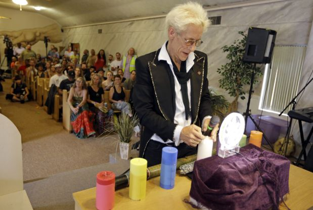 First Church of Cannabis Founder Bill Levin lights candles on the alter during the church's first service, Wednesday, July 1, 2015, in Indianapolis. Levin said he decided to keep marijuana out of Wednesday's service to ensure he can test the Indiana religious objections law in civil court instead of on criminal grounds. (AP Photo/Michael Conroy)