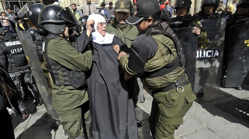 Activistas de un colectivo feminista, disfrazadas de monjas embarazadas, manifestaron este lunes contra la visita que el Papa Francisco iniciará a Bolivia el miércoles próximo y fueron reprimidas por la policía. (Foto: AFP)