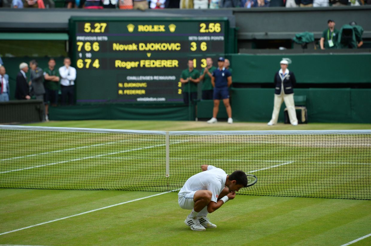 Serbia's Novak Djokovic celebrates beating Switzerland's Roger Federer by eating a blade of grass during their men's singles final match on Centre Court on day thirteen of the 2015 Wimbledon Championships at The All England Tennis Club in Wimbledon, southwest London, on July 12, 2015. Djokovic won the match 7-6, 6-7, 6-4, 6-3.   RESTRICTED TO EDITORIAL USE  --  AFP PHOTO / GLYN KIRK