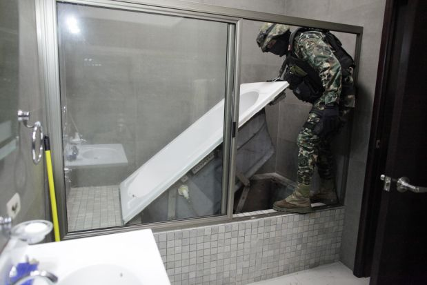 RNPS - REUTERS NEWS PICTURE SERVICE - PICTURES OF THE YEAR 2014A Mexican marine lifts a bathtub that leads to a tunnel and exits in the city's drainage system at one of the houses of Joaquin