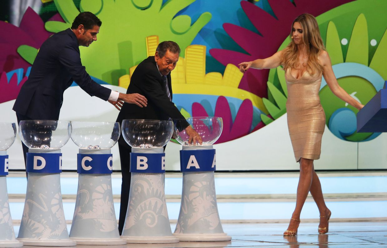 Former soccer great and World Cup winner Alcides Ghiggia of Uruguay is supported by former World Cup player Fernando Hierro of Spain, left, and Brazilian actress Fernanda Lima, right, during the draw ceremony for the 2014 soccer World Cup in Costa do Sauipe near Salvador, Brazil, Friday, Dec. 6, 2013. (AP Photo/Silvia Izquierdo)