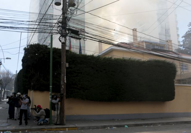 A view shows smoke at the German Embassy, caused by a fire from a stray tear gas canister, during a clash between riot police and striking Potosi mine workers in La Paz, Bolivia July 22, 2015. Miners from the southern Bolivian department of Potosi have been on strike for more than two weeks. They are demanding that President Evo Morales fulfill promises to build infrastructure and create jobs in their region. REUTERS/David Mercado