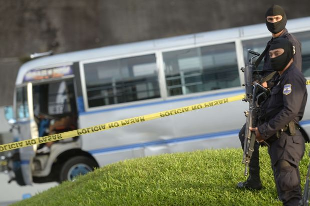 Police guard the site where a bus driver was murdered in San Salvador on July 29, 2015 during the third day of a transport strike over the lack of security in the violence-plagued country. Street gangs in El Salvador killed a seventh bus driver Wednesday for defying their campaign to shut down public transportation and force the government to recognize the feared urban posses. The gangs called for the boycott on Monday, ordering bus drivers to stay off the roads. They killed five defiant drivers that day and another on Sunday. The powerful and ultra-violent gangs want the government to include them in the Security Council. This government body is working with civil society groups to stem the criminal violence that is rampant in this poor country of Central America. AFP PHOTO / MARVIN RECINOS
