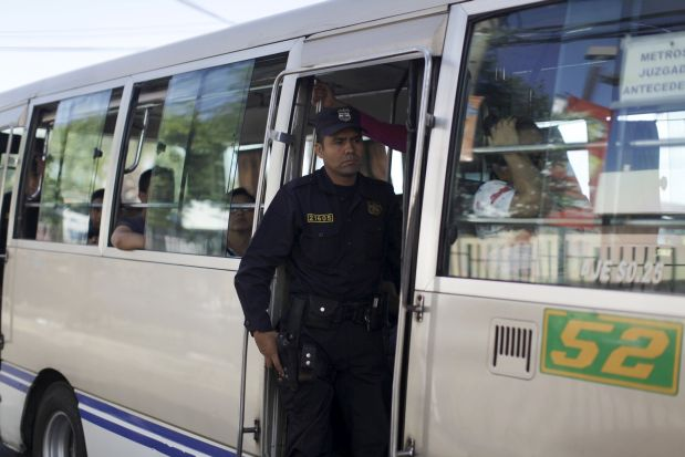 A policeman guards a microbus during the fourth day of a suspension of public transport services in San Salvador, El Salvador July 30, 2015. Violent gangs in El Salvador lifted the order to bus drivers to strike since Monday in a conflict that has killed six people and left thousands of commuters stranded on the streets of the Central American capital, according to local media. REUTERS/Jose Cabezas