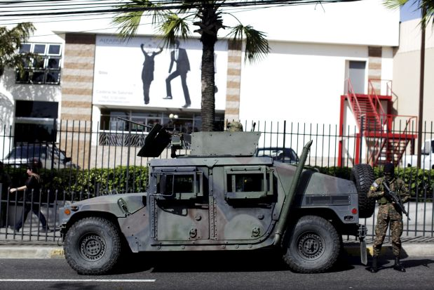 An army vehicle patrols near a shopping mall during the fourth day of a suspension of public transport services in San Salvador, El Salvador July 30, 2015. Violent gangs in El Salvador lifted the order to bus drivers to strike since Monday in a conflict that has killed six people and left thousands of commuters stranded on the streets of the Central American capital, according to local media. REUTERS/Jose Cabezas