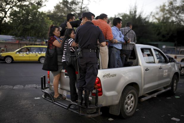 People ride in the back of of a goverment pick up truck during the fourth day of a suspension of public transport services in San Salvador, El Salvador July 30, 2015. Violent gangs in El Salvador lifted the order to bus drivers to strike since Monday in a conflict that has killed six people and left thousands of commuters stranded on the streets of the Central American capital, according to local media. REUTERS/Jose Cabezas