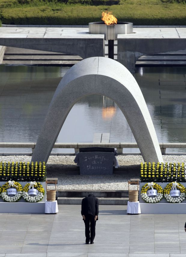 Japanese Prime Minister Shinzo Abe bows in front of the cenotaph dedicated to the victims of the atomic bombing at the Hiroshima Peace Memorial Park during the ceremony to mark the 70th anniversary of the bombing in Hiroshima, western Japan Thursday, Aug. 6, 2015. (AP Photo/Eugene Hoshiko)