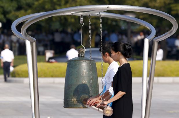 People ring a bell to mark the moment when an atom bomb exploded over Hiroshima 70 years ago during a commemoration ceremony at Peace Memorial Park in Hiroshima, August 6, 2015. Japan on Thursday marks the 70th anniversary of the attack on Hiroshima, where the U.S. dropped an atomic bomb on August 6, 1945, killing about 140,000 by the end of the year in a city of 350,000 residents. It was the world's first nuclear attack. The Atomic Bomb Dome, or Genbaku Dome, was the only structure left standing in this district of the city and has been preserved as a peace memorial. REUTERS/Thomas Peter