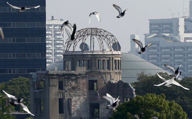 Doves fly over Peace Memorial Park with Atomic Bomb Dome in the background, at a ceremony in Hiroshima, western Japan, August 6, 2015, on the 70th anniversary of the atomic bombing of the city. Japan on Thursday marked the 70th anniversary of the attack on Hiroshima, where the U.S. dropped an atomic bomb on August 6, 1945, killing about 140,000 by the end of the year in a city of 350,000 residents. It was the world's first nuclear attack. The Atomic Bomb Dome, or Genbaku Dome, was the only structure left standing in this district of the city and has been preserved as a peace memorial.   REUTERS/Toru Hanai