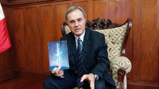 Sixto Paz Wells posando junto a su más reciente libro. (Foto: El Comercio)