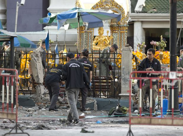 Police investigate a scene the morning after an explosion in Bangkok,Thailand, Tuesday, Aug. 18, 2015. A bomb exploded Monday within a central Bangkok shrine that is among the city's most popular tourist spots killing a number of people and injuring others, police said. (AP Photo/Mark Baker)
