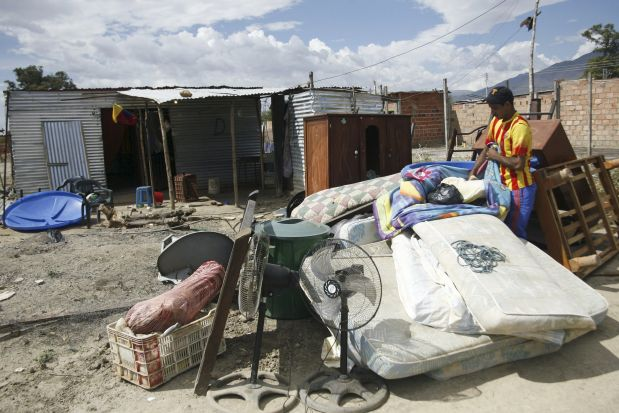 A man carries his belongings next to the houses of people who do not possess proper documentation to live in Venezuela, which have been marked for demolition during a special deployment, at San Antonio in Tachira state, Venezuela, August 24, 2015. Venezuela has stepped up deportations of Colombians, in some cases separating children from their parents, since President Nicolas Maduro ordered the closure of two border crossings last week, Colombia's migration office said on Monday. REUTERS/Carlos Eduardo Ramirez