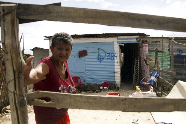 A woman stands in front of the houses of people who do not possess proper documentation to live in Venezuela, which have been marked for demolition during a special deployment, at San Antonio in Tachira state, Venezuela, August 24, 2015. Venezuela has stepped up deportations of Colombians, in some cases separating children from their parents, since President Nicolas Maduro ordered the closure of two border crossings last week, Colombia's migration office said on Monday. REUTERS/Carlos Eduardo Ramirez