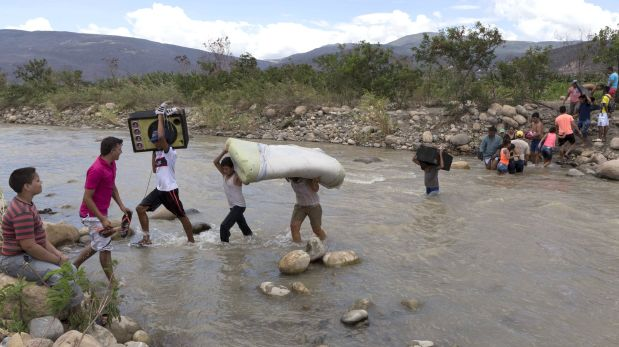 Colombian carry their belongings over from Venezuela as they cross the Tachira river close to Cucuta city, Colombia August 24, 2015. Venezuela has intensified deportations of Colombians since President Nicolas Maduro ordered the closure of two border crossings last week, Colombia's migration office said on Monday, in some cases separating children from their parents. REUTERS/Juan Pablo Cohen-La Opinion/Handout via Reuters  ATTENTION EDITORS - THIS PICTURE WAS PROVIDED BY A THIRD PARTY. REUTERS IS UNABLE TO INDEPENDENTLY VERIFY THE AUTHENTICITY, CONTENT, LOCATION OR DATE OF THIS IMAGE. THIS PICTURE IS DISTRIBUTED EXACTLY AS RECEIVED BY REUTERS, AS A SERVICE TO CLIENTS. FOR EDITORIAL USE ONLY. NOT FOR SALE FOR MARKETING OR ADVERTISING CAMPAIGNS.      TPX IMAGES OF THE DAY