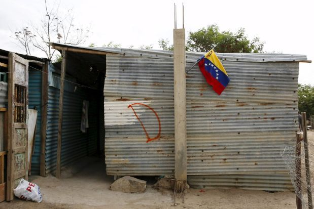 A Venezuelan national flag is seen on a house which has been marked for demolition with the letter D, during a special deployment at San Antonio in Tachira state, Venezuela, August 25, 2015. The ongoing crisis on the border between Colombia and Venezuela should not be used for political point-scoring by leaders in either country ahead of elections in coming months, the Colombian government said on Tuesday. REUTERS/Carlos Garcia Rawlins