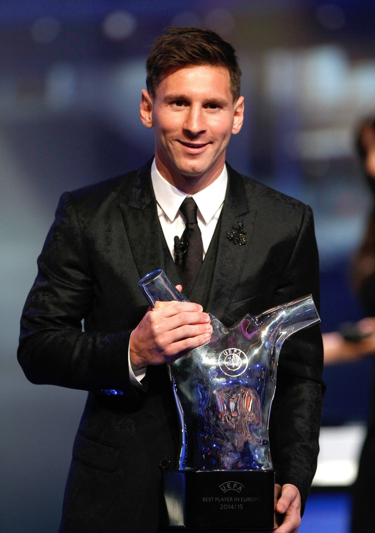 FC Barcelona's Lionel Messi of Argentina, holds his trophy after winning the best player of the year trophy during the UEFA Champions League draw at the Grimaldi Forum, in Monaco, Thursday, Aug. 27, 2015. (AP Photo/Claude Paris)