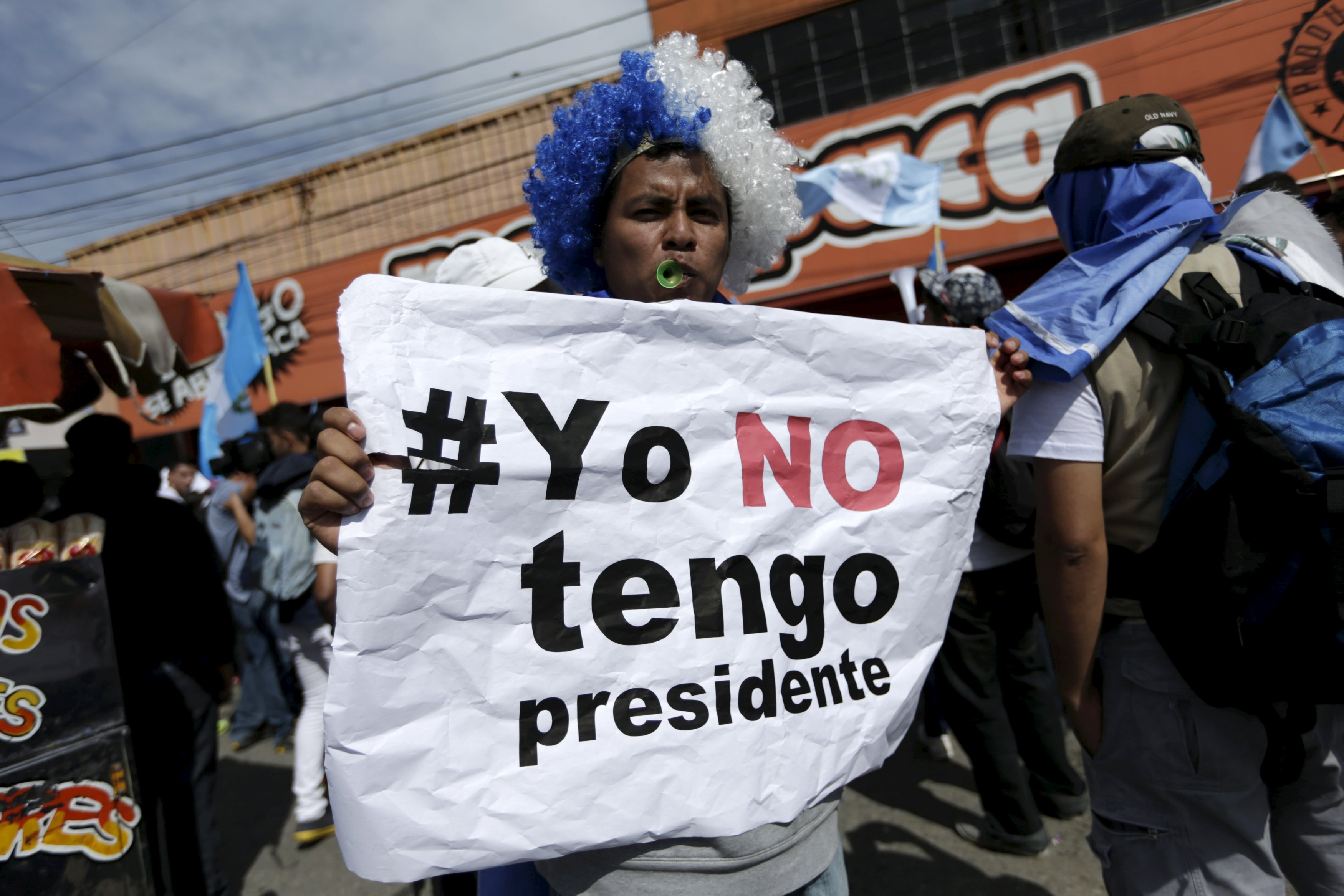 A man wearing a wig with the colours of the Guatemala's flag holds a sign which reads