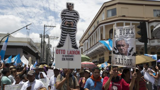 A demonstrator, holding a cutout of Guatemala's President Otto Perez Molina dressed in prison stripes with a message that reads in Spanish: