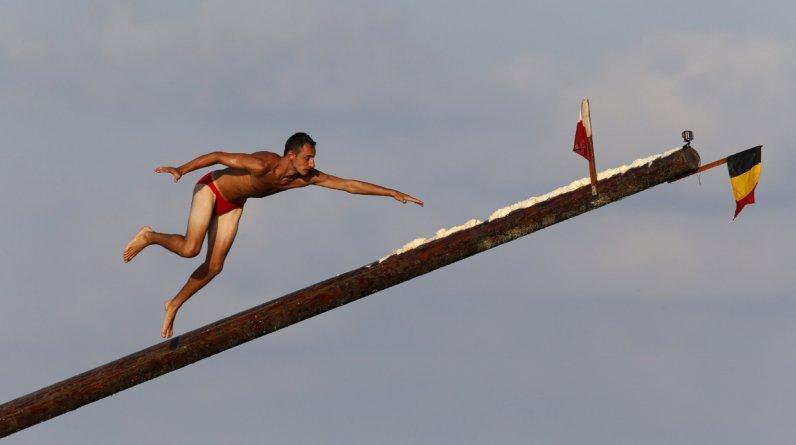 En Malta, un concursante corre sobre la 'gostra', un palo de 20 metros de largo cubierto con grasa, durante las celebraciones en honor a San Julian. Los orígenes del juego se remontan a la Edad Media, cuando jóvenes, mujeres y niños competían por alcanzar las banderas y obtener premios. (Reuters)