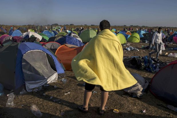 A migrant wraps himslef in a blanket in a makeshift camp at a collection point in the village of Roszke, Hungary, September 8, 2015. REUTERS/Marko Djurica