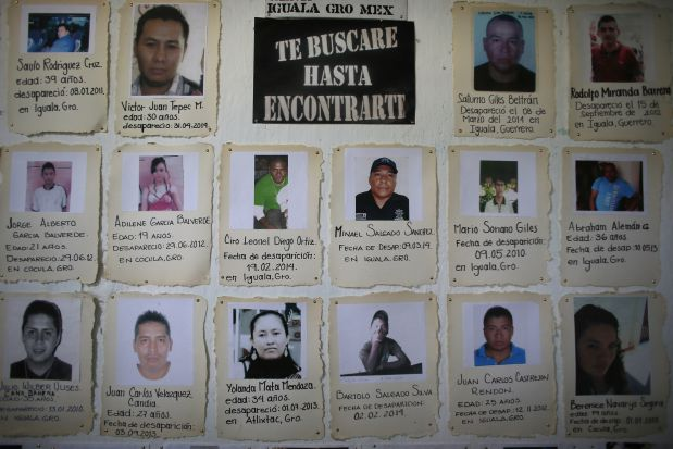 In this April 21, 2015 photo, snapshots with brief descriptions of missing people are tacked to a board in the San Gerardo Catholic Parish in Iguala, Mexico. Little attention had been paid to the many people who have disappeared or been kidnapped in this region until 43 students from a rural teachers college disappeared in Iguala, Sept. 26, 2014. Two months after the students disappeared, hundreds of families began coming forward to tell their stories, emboldened by the international attention focused on the missing students. (AP Photo/Dario Lopez-Mills)