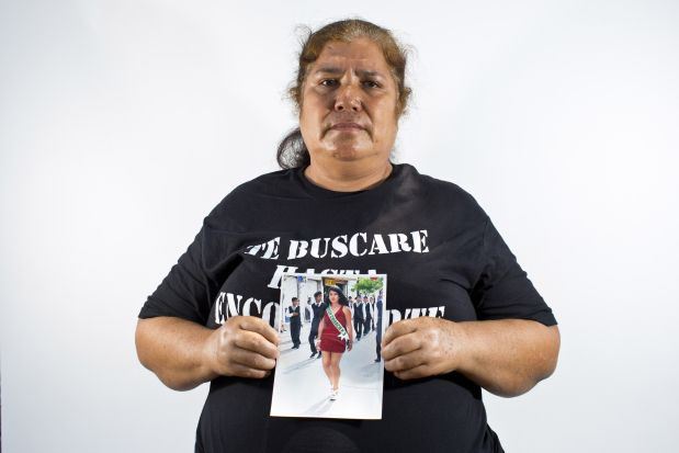 In this May 26, 2015 photo, Rosa Segura Giral holds up a photo of her daughter, Berenice Navarijo Segura, in Iguala, Mexico. On the morning of her high school graduation, 19-year-old Berenice left for a beauty salon appointment, less than a five-minute drive from home, and vanished into the ranks of Mexico?s missing. Segura Giral says she has not lost hope for her daughter. (AP Photo/Dario Lopez-Mills)