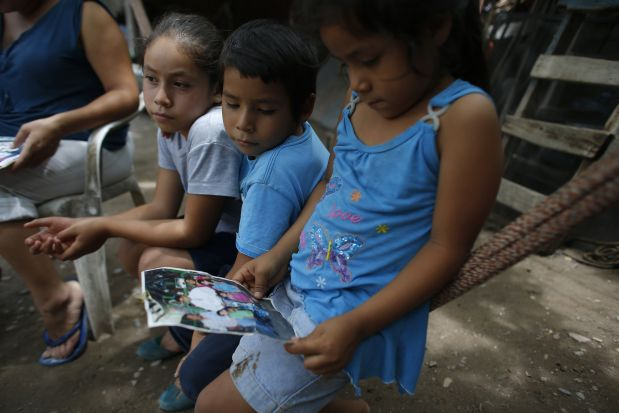 In this June 1, 2015 photo, relatives of Victor Albarran Varela look at a photo of him, at his home in Cocula, Mexico. He is among the 25,000 Mexicans who have disappeared since 2007, according to the government?s count. Victor was 15 years old when he was taken on July 1, 2013. (AP Photo/Dario Lopez-Mills)