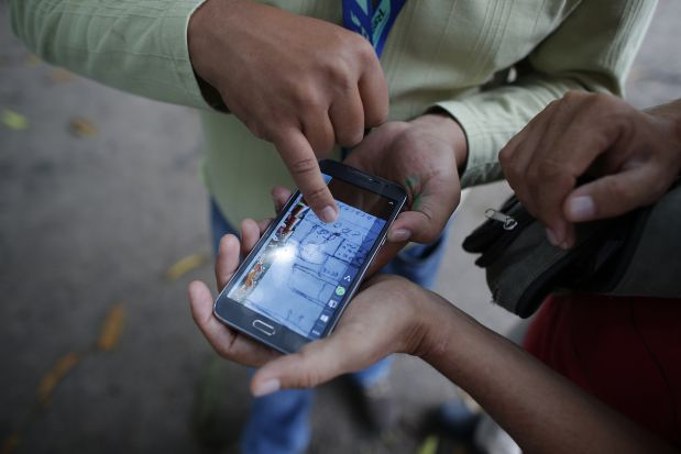 In this May 31, 2015 photo, Mario Vergara Hernandez, right, and another unidentified person look at a hand-drawn map that was sent anonymously to Mario's phone pointing to the possible location of a clandestine grave in Iguala, Mexico. A group of relatives of missing persons in the region has banded together to search for their disappeared loved ones. (AP Photo/Dario Lopez-Mills)