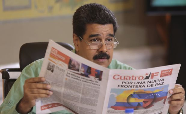 Venezuela's President Nicolas Maduro reads a pro-government newspaper as he speaks during his weekly broadcast