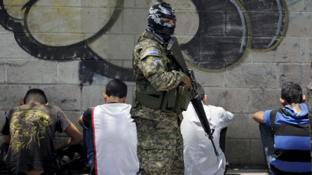 A Salvadoran army soldier watches over a group of suspected members of the Barrio 18 gang, after an attack, in San Salvador April 20, 2015. Three salvadoran soldiers were killed in the last 48 hours after the death of nine Barrio 18 gang members in an army operation this weekend. REUTERS/Jose Cabezas       TPX IMAGES OF THE DAY