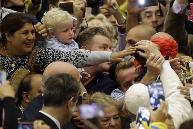 Pope Francis, bottom right, caresses a baby as he arrives for an audience with Roma, Sinti and others itinerant group members, at the Vatican, Monday, Oct. 26, 2015. Pope Francis met Gipsy people from around the world on the occasion of the 50th anniversary of Pope Paul VI visit to a Pomezia gipsy camp in Italy. (AP Photo/Gregorio Borgia)