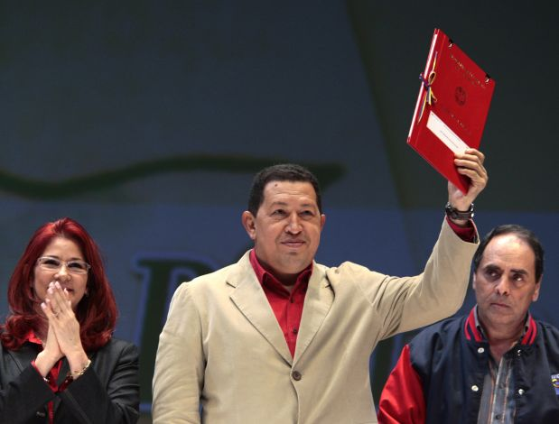Venezuelan President Hugo Chavez (C), with National Assembly President Cilia Flores (L) and Education Minister Hector Navarro standing next to him, holds up a copy of the new education law in Caracas August 15, 2009. REUTERS/Miraflores Palace/Handout (VENEZUELA POLITICS EDUCATION) FOR EDITORIAL USE ONLY. NOT FOR SALE FOR MARKETING OR ADVERTISING CAMPAIGNS