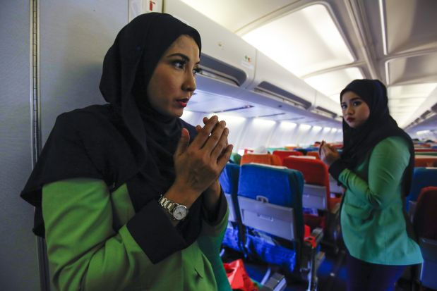 In this Dec. 22, 2015, photo, Rayani Air flight crews prays before departure at Kuala Lumpur International Airport 2 in Sepang, Malaysia. The short domestic flight from Malaysia?s biggest city Kuala Lumpur begins with a recital of Prophet Muhammad?s supplication before his travel. The passengers - most of them Muslims - cup their hands, as a crew member murmurs a short prayer over the loudspeaker just before take-off. (AP Photo/Joshua Paul)