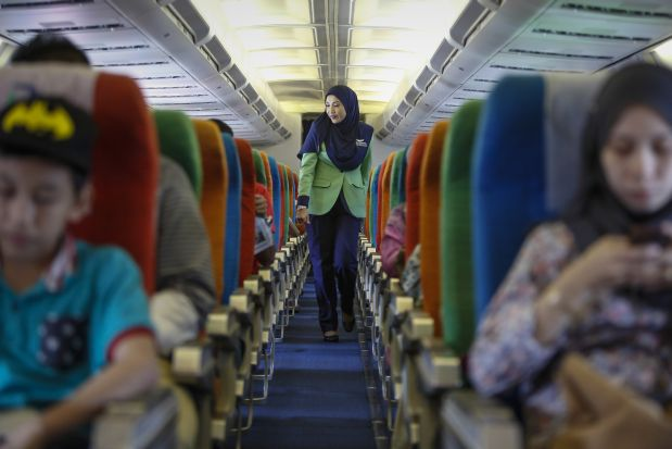 In this Dec. 22, 2015, photo, a Rayani Air flight crew walks down the aisle on board before departure at Kuala Lumpur International Airport 2 in Sepang, Malaysia. Malaysia?s Rayani Air took to the skies over the weekend with a clear bailiwick. It is the country?s first Islamic airline, offering flights that adhere to Islamic rules including prayers, no-alcohol, no-pork meals, and a strict dress code for Muslim female flight attendants. (AP Photo/Joshua Paul)