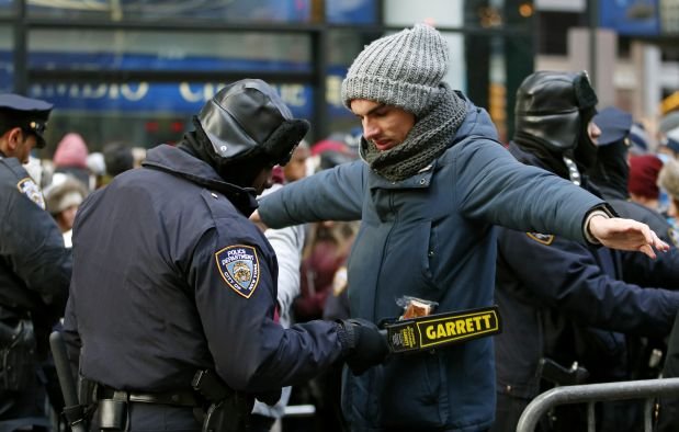 FILE- In this Dec. 31, 2014 file photo, a police officer checks a man entering a cordoned off area on New Year's Eve in Times Square in New York. On Tuesday, Dec. 29, 2015, Police sought to quiet any safety concerns surrounding the New Year?s Eve celebrations for this year?s celebration.