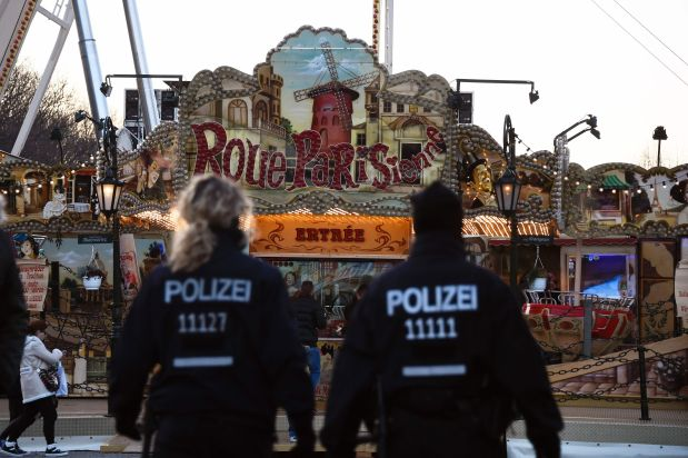 Police patrol at the fair grounds ahead of the New Year's Eve party near the Brandenburg Gate in Berlin on December 31, 2015. / AFP / TOBIAS SCHWARZ