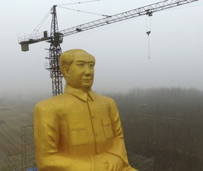 In this Monday, Jan. 4, 2016 photo, scaffolding partially surrounds a 36.6-meter (120-foot) tall gold-colored statue of former Chinese leader Chairman Mao Zedong in Tongxu County in central China's Henan province. According to Chinese state media, businessmen and local villagers contributed nearly 3 million yuan (7,000) to build the cement statue. (Chinatopix via AP) CHINA OUT