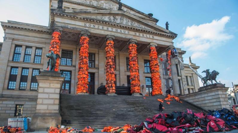 Cientos de los chalecos salvavidas naranjas usados por los refugiados para alcanzar las costas europeas cubren las columnas del Konzerthaus de Berlín, como parte de una instalación del artista y activista chino Ai Weiwei en recuerdo a millones de personas que huyen de la guerra. (AFP)