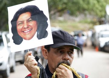 A man holds up a cutout portrait of slain Honduran indigenous leader and environmentalist Berta Caceres outside the coroners office in Tegucigalpa, Honduras, Thursday, March 3, 2016. Caceres, a Lenca indigenous activist who won the 2015 Goldman Environmental Prize for her role in fighting a dam project, had previously complained of receiving death threats from police, soldiers and local landowners because of her work. (AP Photo/Fernando Antonio)