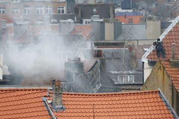Belgium police officer secures the area from a rooftop at the scene where shots were fired during a police search of a house in the suburb of Forest near Brussels, Belgium, March 15, 2016. REUTERS/Francois Lenoir