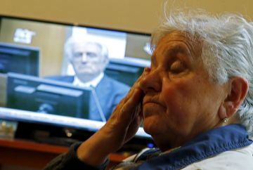 Vasva Smajlovic cries as she watches on television the genocide trial of former Bosnian Serb leader Radovan Karadzic over the 1995 Srebrenica massacre as he appears before the U.N. tribunal in The Hague, as they gather at Smajlovic's house in Potocari near Srebrenica March 24, 2016. REUTERS/Dado Ruvic
